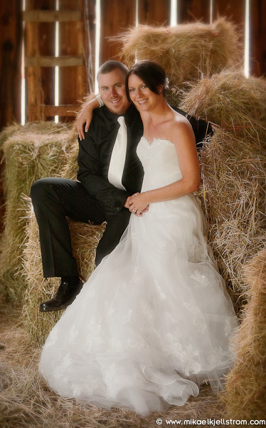 Bride and Groom by hay during farm wedding